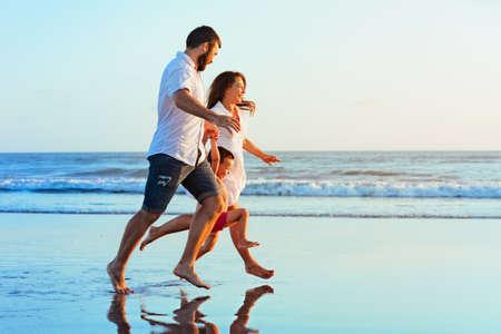 Glückliche Familie - Vater, Mutter, Baby-Sohn den Händen halten, laufen zusammen mit Spritzern von Wasserbecken entlang Sonnenuntergang Meer surfen auf schwarzem Sandstrand. Reise, aktiven Lebensstil, Eltern mit Kind auf Sommerurlaub.
