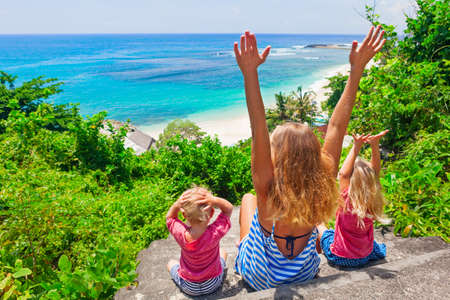 the grand daughter: Happy family travel - mother, baby son, daughter sit on cliff steps, look at sea surf on white sand beach. Active parent lifestyle, people outdoor activity on summer vacation with child on Bali island