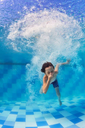 Funny portrait of boy swimming and diving in blue pool with fun - jumping deep down underwater with splashes and foam. Family lifestyle and summer children water sports activity with parents.