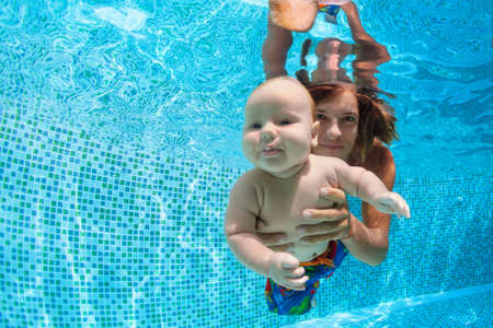 Family fitness - father hold in hands baby son learning swim, dive underwater with fun in pool. Active parent lifestyle, water sport activity, weekend aqua classes, children swimming lesson.