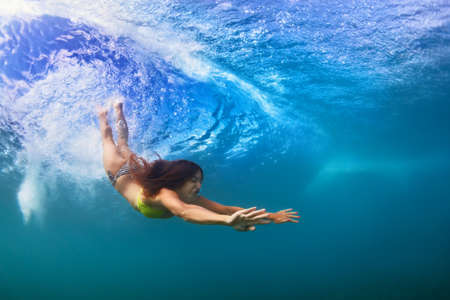 Young sportive girl in bikini in action. Fit woman swim underwater, dive under breaking ocean wave. Healthy lifestyle. Water sports, extreme surfing in outdoor adventure camp on summer beach vacation Stock Photo
