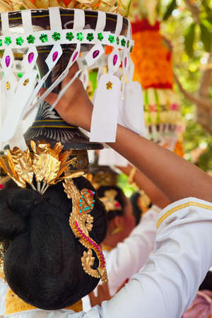 traditional costume: Group of beautiful Balinese women in costumes - sarong, carry offering for Hindu ceremony. Traditional dances, arts festivals, culture of Bali island and Indonesia people. Indonesian travel background