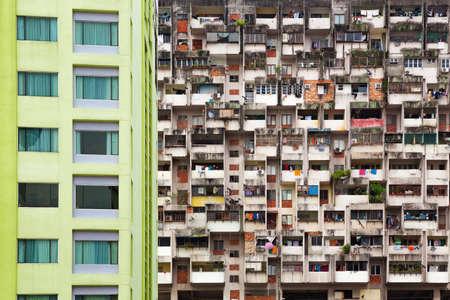 Geometrisch patroon van meerdere appartementencomplex met een groep van ramen en huurder hout op de balkons. Aziatische steden straat achtergrond. Goedkope accommodatie, sociale problemen in overbevolkte landen.