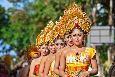 DENPASAR, BALI ISLAND, INDONESIA - JUNE 11, 2016: Group of Balinese people. Beautiful dancer women in traditional costumes dance on street parade at art and culture festival. Фото со стока - 69415200