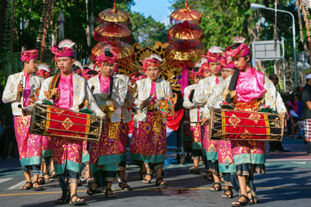 DENPASAR, BALI ISLAND, INDONESIA - JUNE 11, 2016: Group of Balinese people. Beautiful kids in colorful costumes play traditional gamelan music on street parade at art and culture festival. Editorial