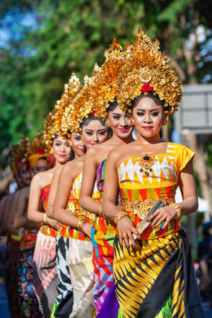 DENPASAR, BALI ISLAND, INDONESIA - JUNE 11, 2016: Group of Balinese people. Beautiful dancer women in traditional costumes dance on street parade at art and culture festival. 에디토리얼