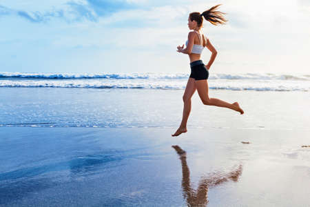 Active sporty woman run along ocean surf by water pool to keep fit and health. Sunset black sand beach background with sun. Woman fitness, jogging workout and sport activity on summer family holiday. Stock Photo