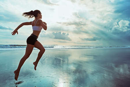Active sporty woman run along ocean surf by water pool to keep fit and health. Sunset black sand beach background with sun. Woman fitness, jogging workout and sport activity on summer family holiday. Foto de archivo