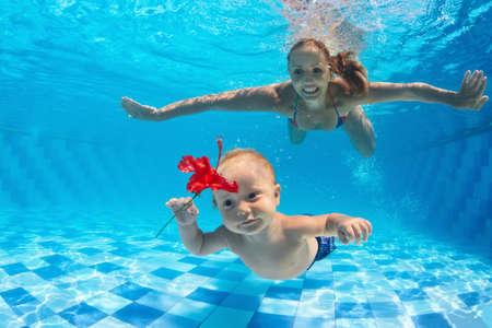 Family fitness - de gelukkige moeder, actieve babyzoon leren zwemmen, duiken onder water met plezier in het zwembad. Actieve ouders gezonde levensstijl, watersport activiteiten, kinderen aqua klassen, kinderen zwemmen les.