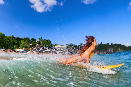 Girl in bikini has fun on surf board - woman surfer run into water, jump with splashes through ocean wave. People in water sport adventure camp, beach extreme activity on summer beach family vacation.