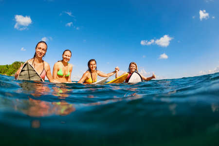 Happy girls in bikini have fun - group of surfers sit on surf boards, young women wait for big ocean wave. People in water sport adventure camp, beach extreme activity on summer beach family vacation