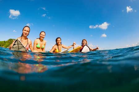Glada tjejer i bikini ha kul - grupp surfare sitta p� surfingbr�dor, unga kvinnor v�nta stor ocean wave. M�nniskor i vattensport �ventyr l�ger, strand extrem aktivitet p� sommar strand semester med familjen Stockfoto
