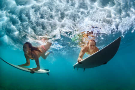 Group of active girls in action. Surfer women with surf board dive underwater under breaking big wave. Healthy lifestyle. Water sport, extreme surfing in adventure camp on family summer beach vacation