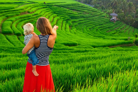Beautiful view of Balinese traditional fields. Nature walk in green rice terrace. Happy mother hold happy little baby traveler.  Travel adventure with child, family summer vacation in Bali, Indonesia