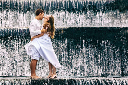 honeymooner: Happy family on honeymoon holidays - married loving couple hugging, kissing with fun under falling water in cascade waterfall pool. Active lifestyle, people travel on summer vacation on Bali island.