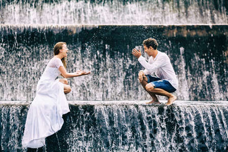honeymooners: Happy family on honeymoon holidays - married loving couple splashing with fun under falling water in cascade waterfall pool. Active lifestyle, people travel activity on summer vacation on Bali island.