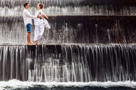 honeymooners: Happy family on honeymoon holidays - married loving couple hugging, kissing with fun under falling water in cascade waterfall pool. Active lifestyle, people travel on summer vacation on Bali island.