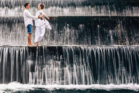falling water: Happy family on honeymoon holidays - married loving couple hugging, kissing with fun under falling water in cascade waterfall pool. Active lifestyle, people travel on summer vacation on Bali island.