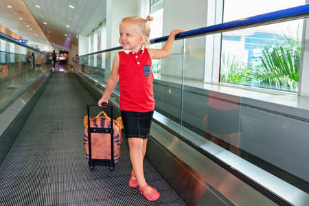 air plane: Happy little child with luggage stand on airport transit hall walkway moving to plane departure gate for waiting flight boarding. Active family lifestyle, travel by air with kid on summer holiday tour