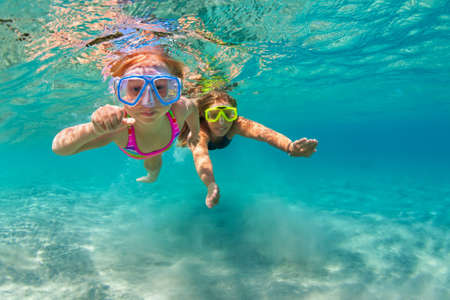 Happy family - mother with baby girl dive underwater with fun in sea pool. Healthy lifestyle, active parent, people water sport outdoor adventure, swimming lessons on beach summer holidays with child Standard-Bild