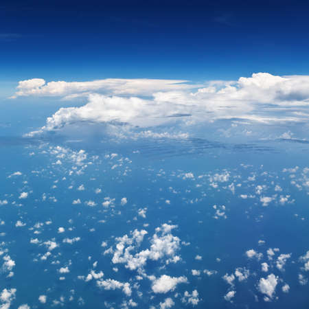 white fly: Clear blue sky. Aerial view from passenger cabin through plane window. Aircraft fly in mid air. Flight above ocean and beautiful white cloud. Vacation tour, travel background with copy space Stock Photo