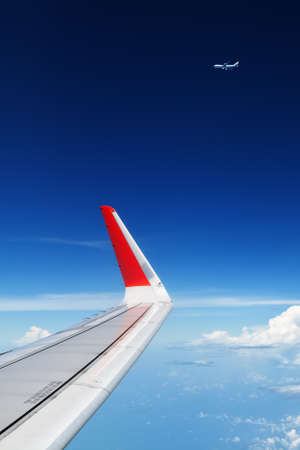 Oncoming flight traffic in mid air. Aircraft flying above beautiful earth, clouds. Aerial view of clear blue sky, aircraft wing from cabin through plane window. Travel tour background with copy space