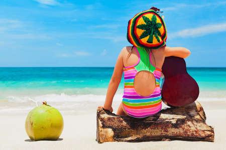 Little happy baby girl in rastaman hat has fun, play reggae music on Hawaiian guitar, enjoy caribbean beach party. Children healthy lifestyle. Travel, family activity on Jamaica island summer holiday