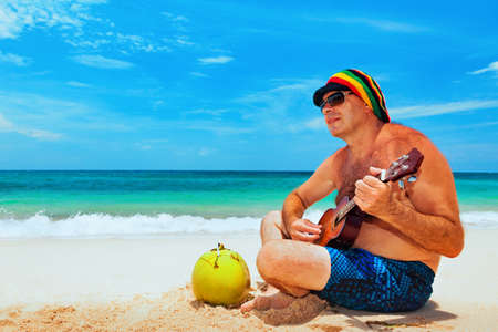 Happy retiree age man in funny hat has fun, play reggae music on Hawaiian guitar, enjoy caribbean beach party. Seniors lifestyle and leisure. Travel family activity on Jamaica island summer holiday. Stockfoto
