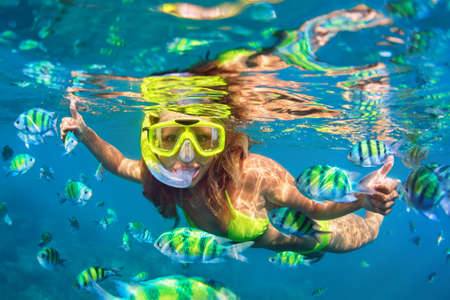 Happy family - girl in snorkeling mask dive underwater with fishes school in coral reef sea pool. Travel lifestyle, water sport outdoor adventure, swimming lessons on summer beach holidays with child. Stockfoto
