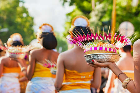 Group of beautiful Balinese women in costumes - sarong, carry offering for Hindu ceremony. Traditional dances, arts festivals, culture of Bali island and Indonesia people. Indonesian travel background