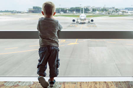 Little baby boy waiting boarding to flight in airport transit hall and looking through the window at airplane near departure gate. Active family lifestyle, travel by air with child on summer vacation