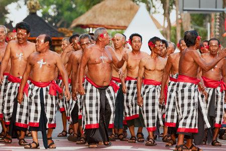 DENPASAR, BALI ISLAND, INDONESIA - JUNE 11, 2016: Group of Balinese senior people. Beautiful dancer men in traditional kecak dance costumes on street parade at art and culture festival.