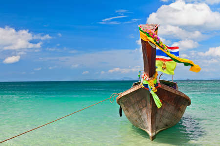 Travel background. Beautiful Thailand tropical sand beach view with decorated traditional longtail boat. Vacation day tour from Phuket to Ko Phi Phi Don island, Phi Phi archipelago, Krabi, Andaman Sea Stock Photo
