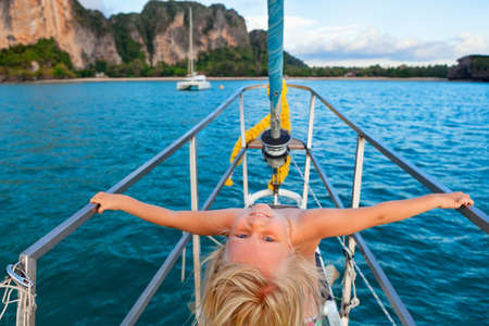 Joyful child portrait. Happy little baby girl on board of sailing yacht have fun discovering islands in tropical sea on summer coastal cruise. Travel adventure, yachting with kids on family vacation. Stock Photo