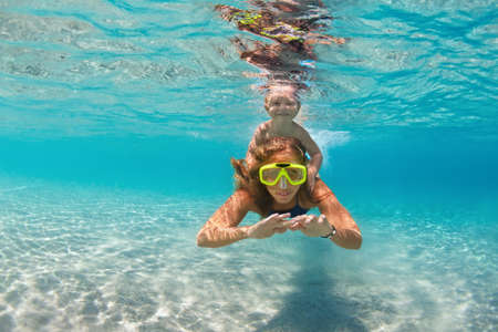 Happy active family - mother, baby son snorkel and dive together underwater in sea pool. Healthy people lifestyle, water sport outdoor adventure, swimming lesson on summer beach vacation with child 스톡 콘텐츠