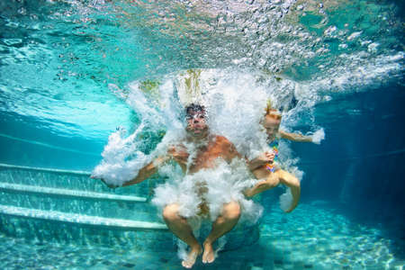 Happy family - father, baby daughter swim and dive in swimming pool with fun - jump deep down underwater with splashes. Lifestyle, summer children water sport activity and swimming lessons with parent Stock Photo