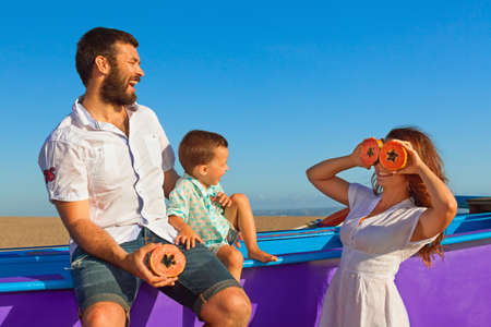 Happy funny family - father, mother, baby son walk together by sea sand beach. People have picnic - eat tropical fruit papaya with fun. Travel, active lifestyle, parents with child on summer holiday. Stock Photo