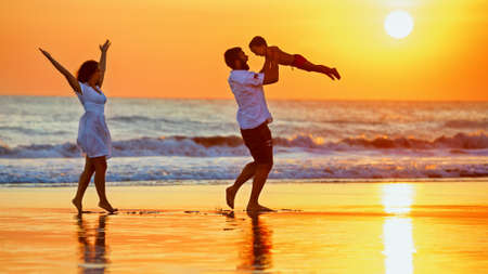 Happy family - father, mother, baby son walk with fun along edge of sunset sea surf on black sand beach. Active parents and people outdoor activity on summer vacations with children on Bali island photo