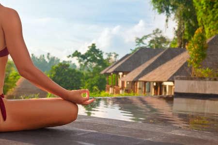 Goedemorgen met yoga mediteren op zonsopgang achtergrond. Actieve vrouw in bikini te oefenen op villa aan het zwembad om fit en gezond te houden. Vrouw fitness, sport activiteit in de zomer vakantie met het gezin.