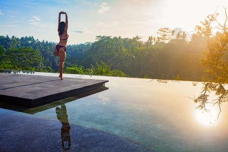 Buenos días con el yoga meditación en el amanecer de fondo. Mujer activa en bikini practicando en villa junto a la piscina para mantenerse en forma y salud. entrenamiento de la aptitud de la mujer, la actividad deportiva en vacaciones de verano en familia.