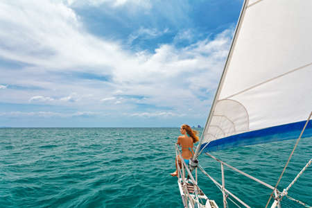 Joyful young woman portrait. Happy girl on board of sailing yacht have fun discovering islands in tropical sea on summer coastal cruise. Travel adventure, yachting with kids on family vacation.