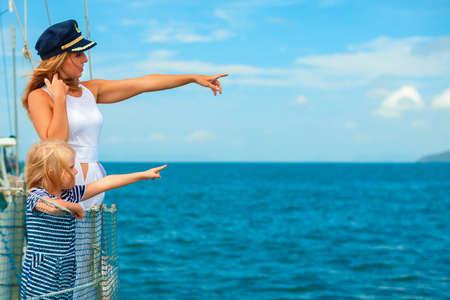 Gelukkige familie aan boord. Moeder in captain cap, kleine dochter aan boord van zeiljacht. Kinderen hebben plezier in het ontdekken van eilanden in de zomervakantie. Reis avontuur, jagen met kinderen op familie vakantie.
