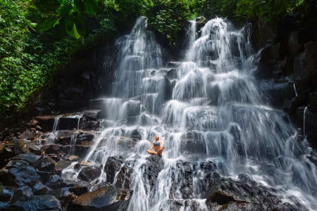 Travel in Bali jungle. Beautiful young woman sit in zen-like yoga pose under falling spring water, enjoy tropic cascade waterfall. Nature day trip, walking adventure, fun on family summer vacation