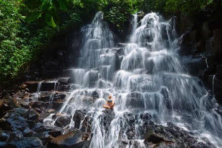 Travel in Bali jungle. Beautiful young woman sit in zen-like yoga pose under falling spring water, enjoy tropic cascade waterfall. Nature day trip, walking adventure, fun on family summer vacation