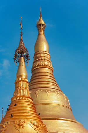 View of Myanmar temple spire. Popular place to visit at Yangon city tour - pagoda Shwedagon with Buddha scared relics. Famous travel destination in Asia. Traditional Burmese art and culture background Stock Photo