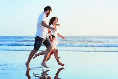 Happy family - father, mother, baby son hold hands, run together with splashes by water pool along sunset sea surf on black sand beach. Travel, active lifestyle, parents with child on summer vacation. photo