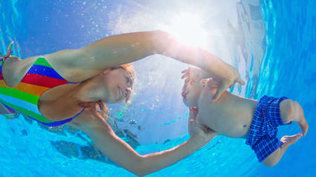 infant school: Happy family has fun. Underwater photo. Mother teach to swim and dive baby son in swimming pool. Healthy lifestyle, active parent, people water sport and lessons on beach summer holiday with child.