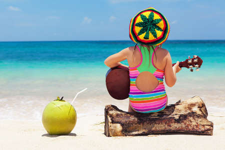 Little happy baby in rastaman hat have fun, play reggae music on Hawaiian guitar, enjoy relaxing on ocean beach. Children healthy lifestyle. Travel, family activity on tropical island summer holiday Stock Photo