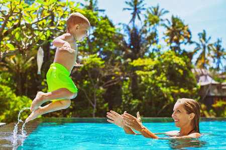 Happy child in action - active kid swim with fun in swimming pool. Baby son jump high to mother catching hands. Healthy family lifestyle, summer vacation water sports activity and lessons with parents Stock Photo