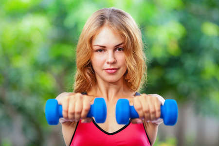 get a workout: Active sporty woman doing morning exercises with dumbbells at home. Workout plan to get summer beach body. Healthy lifestyle, fitness exercises to keep fit, loss weight and shaping perfect slim body.